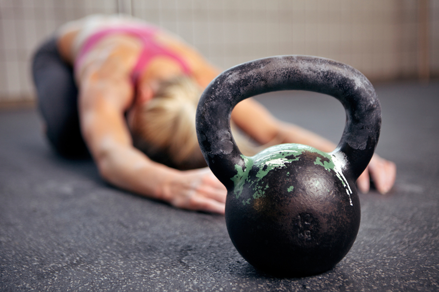 woman stretching and kettlebell